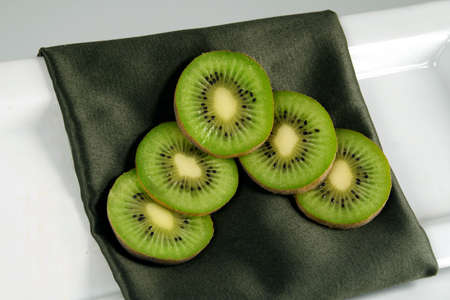 An arrangement of kiwi on a decorative green napkin on a white plate against a white background.