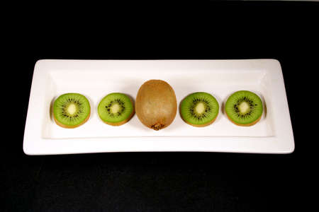 Kiwi arranged on a white plate with a black background. Stock Photo