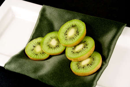 An arrangement of kiwi on a decorative green napkin on a white plate with a black background. Stock Photo