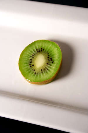 A slice of kiwi arranged on a white plate with a black background. Stock Photo