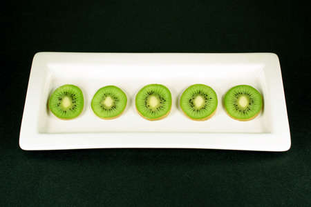 Slices of kiwi arranged on a white plate with a black background.