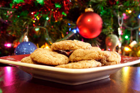 A plate of cookies in front of a Christmas tree.