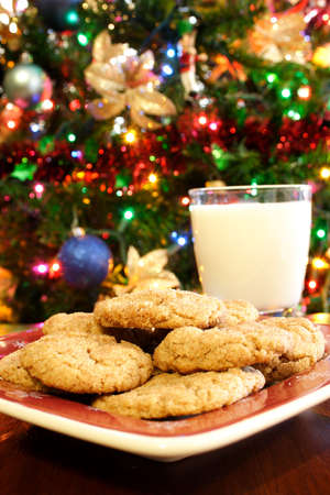 A plate of cookies and a glass of milk in front of a Christmas tree.