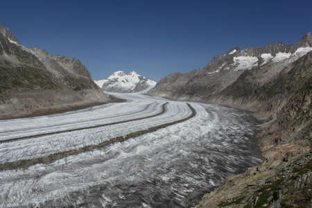 aletsch: Aletsch Glacier, Switzerland with blue sky and a curving mountain range framing the glacier Stock Photo