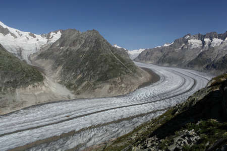 aletsch: View Over Aletsch Glacier, Switzerland   Taken from the overlooking mountainside in Summer, with a blue sky and mountains bordering the glacier