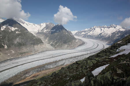 aletsch: View of Aletsch Glacier, Switzerland in June 2013   With a rocky mountainous border and a blue sky with scattered clouds  Stock Photo