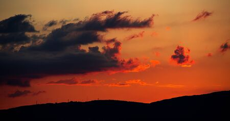 a fiery sunset in the clouds goes behind the mountains. bright summer landscape in the resort of gelendzhik