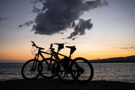 Two mountain bikes stand on the edge of a cliff, where you can see a bright orange sea sunset, mountains and large clouds. Recreation and sports in the resort city of Gelendzhik