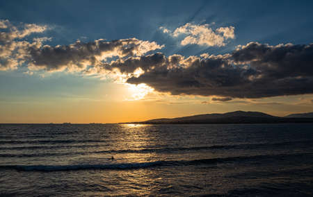 Colorful sea sunset, clouds have hidden the sun, but its bright rays fall on the sea surface. Mountains and cargo ships can be seen on the horizon. Bay of the resort city of Gelendzhik