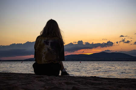 A young girl is sitting on a sandy beach, completely alone and watching the sunset. Dramatic summer landscape, calm sea, and mountains, behind which the sun has gone