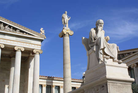 Academy of Athens: part of the main building with ionic columns, statue of god Apollo on top of a pillar with his lyre and ancient Greek philosopher Socrates sitting. This neoclassical construction is one of the major landmarks of Athens. Stock Photo
