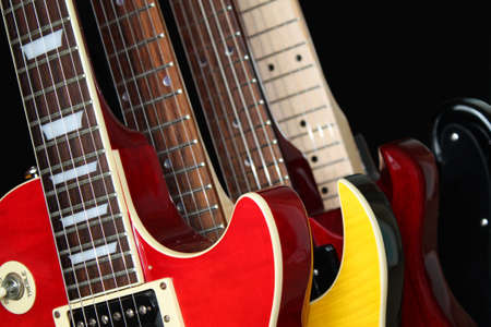 Closeup of four electric guitars isolated over a black background. Stock Photo