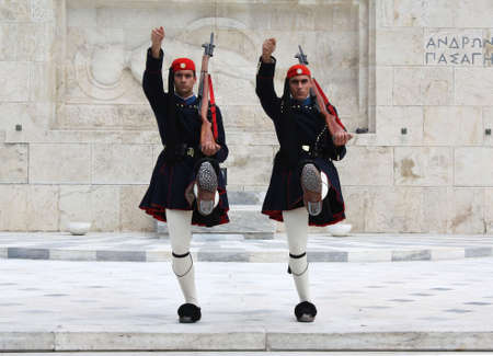 Athens, Greece - April 21, 2009: Evzones (presidential ceremonial guards) in front of the Unknown Soldiers Tomb at the Greek Parliament Building in Athens, opposite Syntagma Square. Editorial