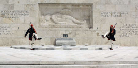 Athens, Greece - April 21, 2009: Evzones (ceremonial guards) in front of the Unknown Soldiers Tomb at the Greek Parliament Building in Athens, opposite Syntagma Square. Evzones guard the Tomb of the Unknown Soldier, the Hellenic Parliament and the Presid