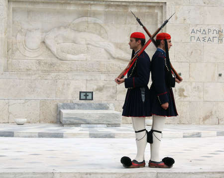 Athens, Greece - April 21, 2009: Evzones (palace ceremonial guards) in front of the Unknown Soldier's Tomb at the Greek Parliament Building in Athens, opposite Syntagma Square. Evzones guard the Tomb of the Unknown Soldier, the Hellenic Parliament and the