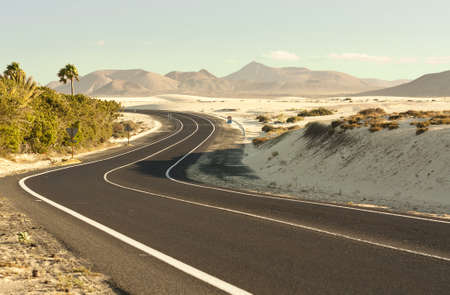 mountain oasis: Winding road across the dunes of Corralejo, Fuerteventura, in the Canary Islands, Spain. Stock Photo