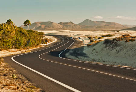 rural road: Winding road across the dunes of Corralejo, Fuerteventura, in the Canary Islands, Spain. Stock Photo