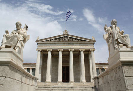 Neoclassical Academy of Athens in Greece showing main building and statues of ancient Greek philosopers Plato (left) and Socrates (right). The statues of goddess Pallas Athena and god Apollo are behind. The Academy of Athens is the highest research establ
