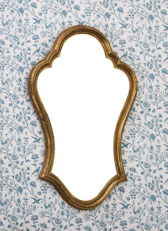 Golden-framed mirror on wallpapered wall with white copy space. photo