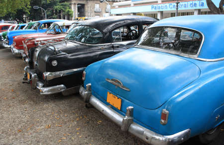 Colourful vintage taxis parked in a street in Havana, Cuba. Rear view.