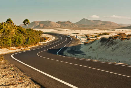 winding road: Winding road across the dunes of Corralejo, Fuerteventura, in the Canary Islands, Spain. Stock Photo