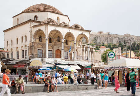 ATHENS, GREECE - MAY 24, 2011: Greece on the verge of bankruptcy. Tourism is a decisive sector of hope for Greek economy. Athenians and tourists in Monastiraki Square, with Tzistarakis Mosque and the Acropolis in the background,