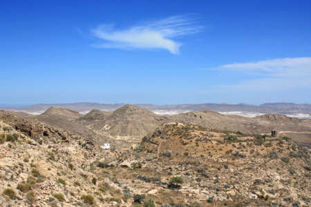 arid climate: Arid landscape in Nijar, with white greenhouses in the background. Province of Almeria, Andalusia, Spain. Stock Photo
