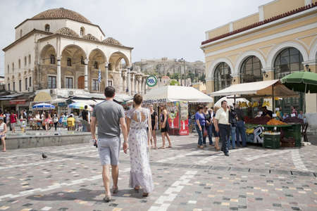 ATHENS, GREECE - MAY 24, 2011: Greece on the verge of bankruptcy. Tourism is a decisive sector of hope for Greek economy. Athenians and tourists in Monastiraki Square, with Tzistarakis Mosque and the Acropolis in the background, Stock Photo - 10559373