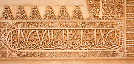 Arabic inscriptions on a wall in the Nasrid Palaces of the Alhambra of Granada, Spain. Editorial