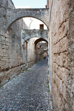 rhodes: Old cobblestone alley in Rhodes Old Town, Greece, with arches and stone facades.