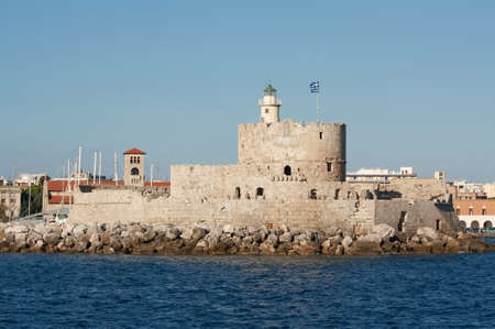 Medieval fortress of Saint Nicholas, now the site of a lighthouse, in Mandraki Harbour, Rhodes New Town, Greece. Stock Photo - 11044802