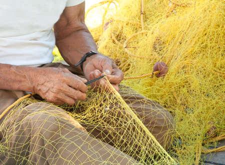 pescador: Un pescador arreglando su red de pesca de color amarillo en su barco en una isla griega.