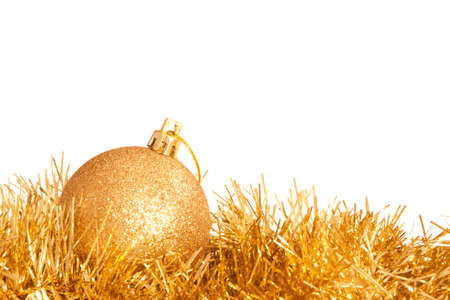 A glittering golden Christmas bauble on some tinsel isolated on white.