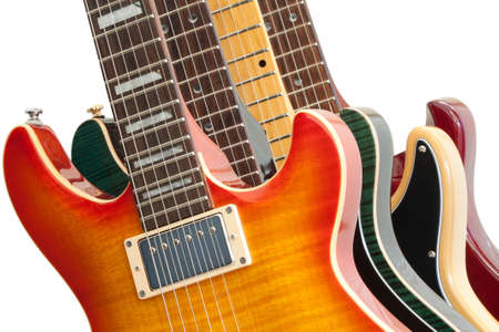 Closeup of four electric guitars on white.