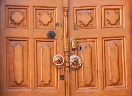 An old-fashioned wooden door with a knocker in the shape of a hand and several keyholes. Stock Photo - 12198404