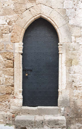 door bolt: Old black wooden medieval door on limestone wall with antique sliding door bolt and padlock.