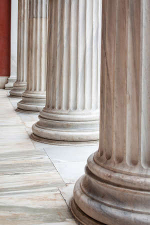 Closeup of row of neoclassical Greek columns in the porch of the archaeological museum of Athens, Greece.