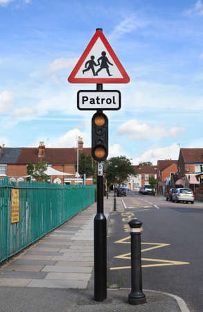 british people: School and school patrol warning traffic sign in a street in England. Editorial