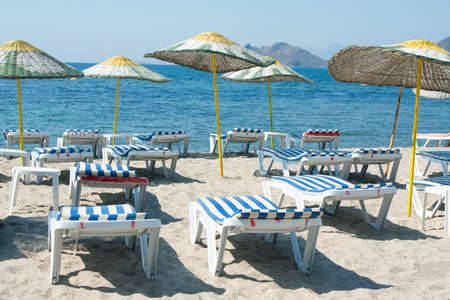 loungers: Sun loungers and wicker parasols on sandy beach in Turgutreis in the Bodrum Peninsula, Turkey