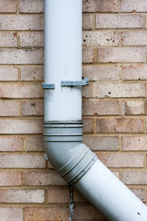 Brown brick wall with grey gutter or drain pipe.