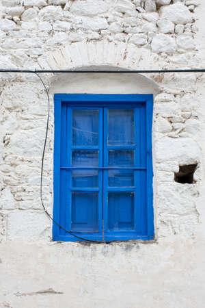 whitewashed: Old blue wooden window on whitewashed stone wall in Turkey.