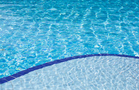 Background of clear blue water with sun reflections in an outdoor swimming pool with two different depths, a shallow and a deep depth. photo