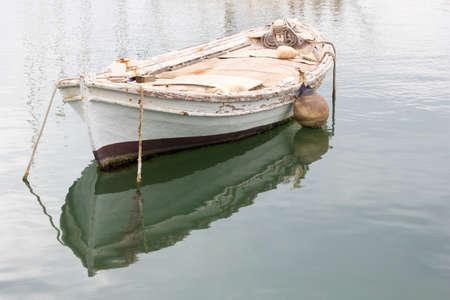 Oude witte verweerde houten roeiboot of sloep afgemeerd in een haven in Griekenland. Stockfoto