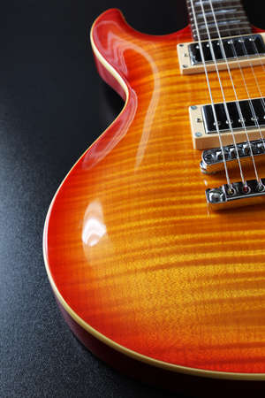 Closeup of electric guitar with cherry sunburst finish and flame maple top  photo