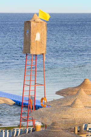watchtower: A wicker lifeguard watchtower or lookout tower and yellow flag on a beach