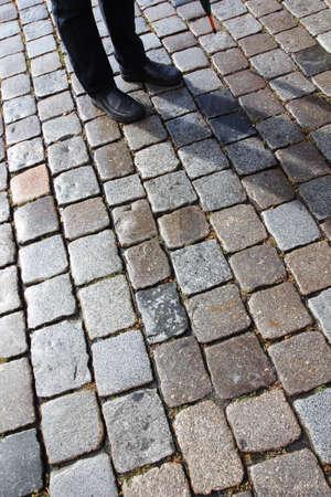 empedrado: El hombre con su sombra en la antigua calle de adoquines, en Nuremberg, Alemania