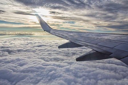 Sunset, cloudy sky and airplane wing as seen through window of an aircraft  photo