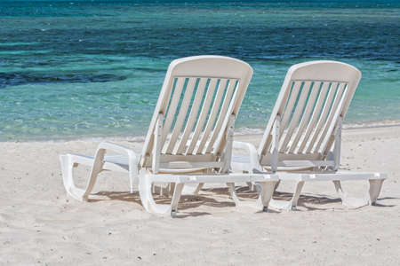 Two white sunbeds on a sandy beach facing the Caribbean Sea  Stock Photo