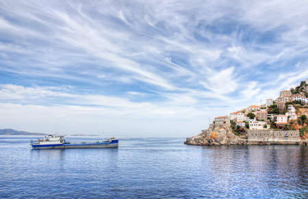 Aegean Sea and Greek island of Hydra or Ydra, a ship, and a dramatic blue and white cloudy sky in the Saronic Gulf, Aegean Sea, Greece  photo