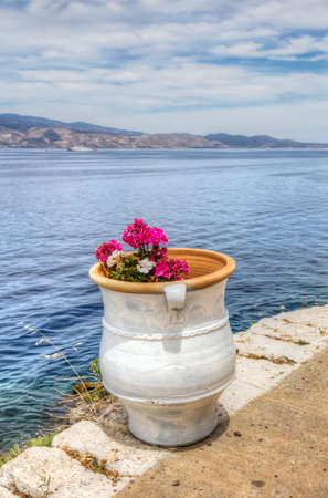 Colourful pink and white flowers in white clay pot overlooking the Saronic Gulf in Hydra island in the Aegean Sea, Greece  Stock Photo